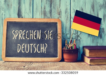a chalkboard with the question sprechen sie deutsch? do you speak german? written in german, a pot with pencils, some books and the flag of Germany, on a wooden desk Stock photo ©