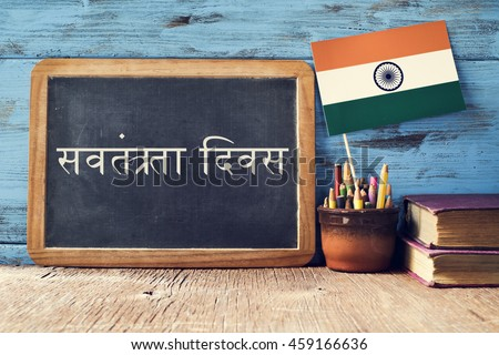 a chalkboard with the text Independence Day written in Hindi and a flag of India, on a rustic wooden surface, against a blue wooden background