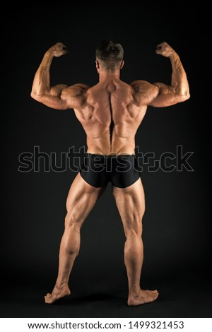A champion bodybuilder. Bodybuilder or muscleman, back view. Strong bodybuilder flexing arms muscles on black background. Fit bodybuilder showing muscular body.