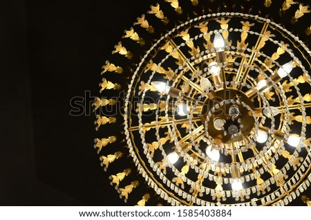 A Chandelier with Lightbulbs Illuminating the Darkness #1585403884