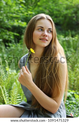 A charming girl poses positively with a blooming dandelion in her hands. A girl is a student of a medical university. #1091475329