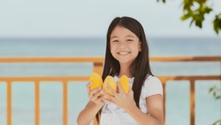 A charming philippine schoolgirl girl in a white dress and long hair positively poses with a mango in her hands. The sun. The blue ocean. Childhood. Recreation.