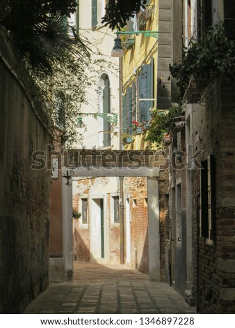 A charming, typical house at the end of a sunlit alley in Venice, Italy.