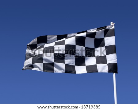 A checkered flag blowing in the wind at the end of a motor race.