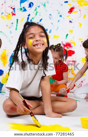 A cheerful African American girl painting