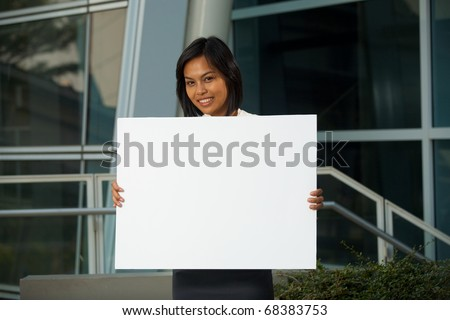 A cheerful and cute corporate professional holds an empty placard in front of an office building.  Custom text insert.  20s female Asian Thai model of Chinese descent.