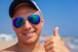 A cheerful and happy tanned man in sunglasses on the beach shows a thumbs up. The reflection in the sunglasses.