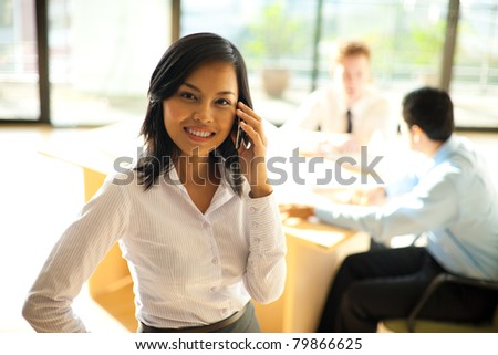 A cheerful asian businesswoman using a smartphone during a meeting with her coworkers