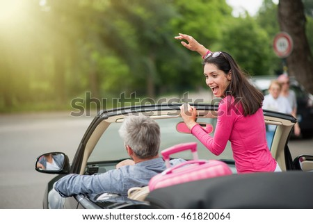 A cheerful couple going on a road trip in their convertible car, there is luggage on the back seat, the man has grey hair,  the brunette woman raising arms standing in the vehicle. Shot with flare