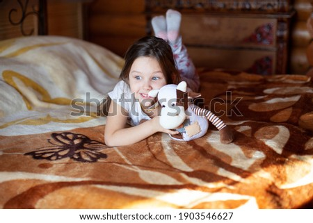 A cheerful, exited girl holds a toy cow and lies on a sunny morning on a bed in the bedroom of a rustic log house. Stock photo ©
