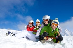 A cheerful family smiling at the camera as they are lying together in the snow with a sled