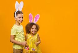 A cheerful girl and boy with rabbit ears on her head with a basket of colored eggs in her hands on a yellow background. They looks away. Funny happy baby. Covid Easter to the child.