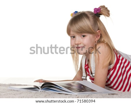 A cheerful girl is reading a book lying on the thick carpet; isolated on the white background