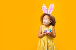 A cheerful girl with rabbit ears on her head and a protective mask with a basket of colored eggs in her hands on a yellow background. She looks away. Funny happy baby. Covid Easter to the child.