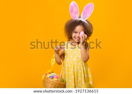 A cheerful girl with rabbit ears on her head with a basket of colored eggs in her hands on a yelow background. Funny crazy happy baby. Easter to the child.