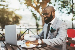 A cheerful handsome bald black businessman in eyeglasses and neat beard is having a coffee break in an outdoor restaurant, pouring himself some tea while reading a chat message on his laptop in front