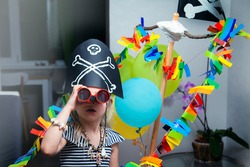 A cheerful little child in a pirate costume plays at home on a cardboard sea ship with a black flag. Fun games at home with family. Travels and adventures at home