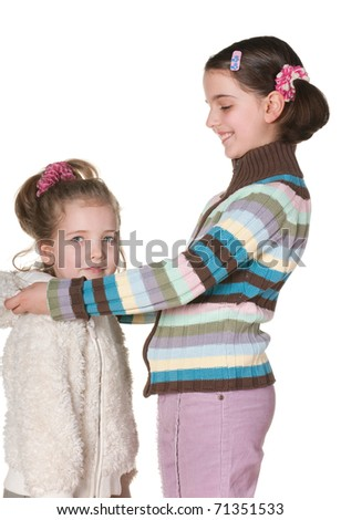 A cheerful little girl assists a little girl to be dressed; isolated on the white background