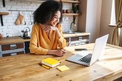A cheerful mixed-race girl uses laptop for remote work or home leisure while sitting in the kitchen at home. Side view a nice girl with an afro hairstyle looks at screen with a smile