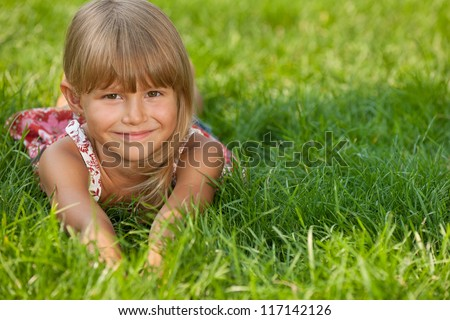A cheerful pretty little girl is lying on the green grass in summer