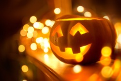 A cheerful smiling Jack O Lantern on halloween placed on a fireplace with fairy lights