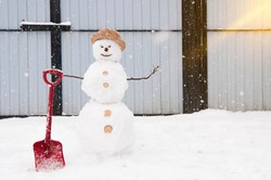 a cheerful snowman in a hat and with a shovel in his hand made of lumps of snow