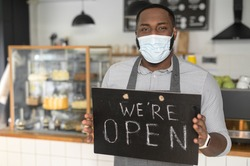 A cheerful young African American male waiter wearing mask holding in hands open sign indoors in own bakery shop. Reopening bakehouse after lockdown, pandemic, epidemic