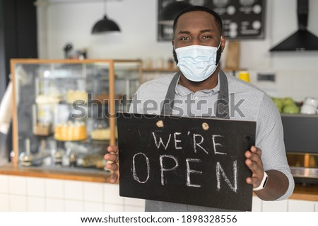 A cheerful young African American male waiter wearing mask holding in hands open sign indoors in own bakery shop. Reopening bakehouse after lockdown, pandemic, epidemic Foto d'archivio ©
