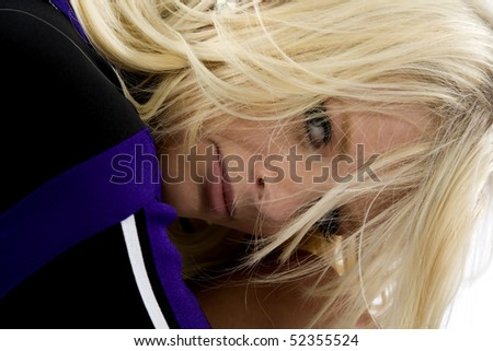 A cheerleader has her head on her knee and a serious face