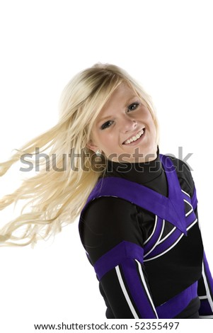 A cheerleader is flipping her hair and smiling