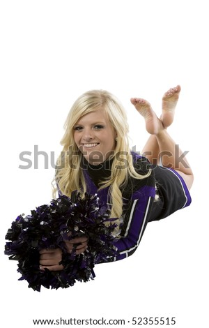 A cheerleader is laying with her pom poms in front of her and her legs up and crossed