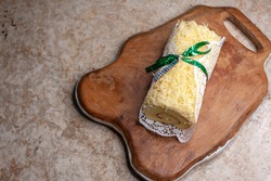 A cheese roll cake is wrapped in doily paper and tied with a green bow on wooden board, ready to be packed.