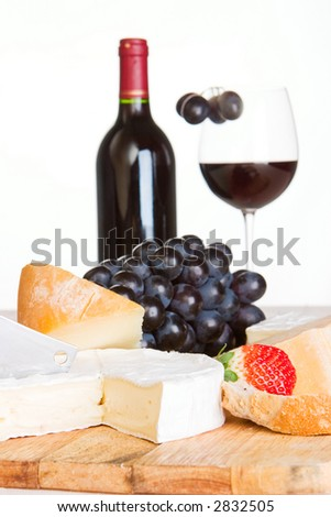 A cheese selection with a bottle and half a glass of red wine in the background