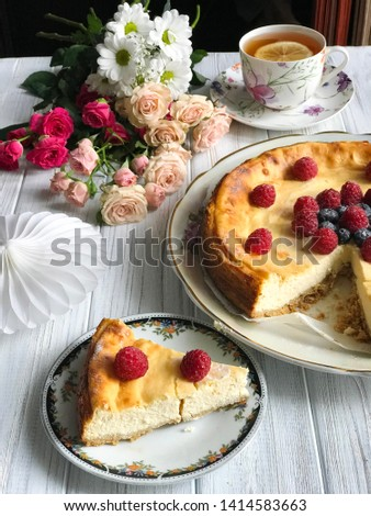 A cheesecake with blueberries and rasberries, a cup of tea with lemon and bunch of flowers on light wooden background. Beautiful delicious morning concept. Food blog recipe picture, sweets shop ad.