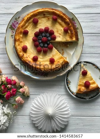 A cheesecake with blueberries and rasberries and bunch of flowers on light wooden background. Beautiful delicious morning concept. Food blog recipe picture, sweets shop ad.