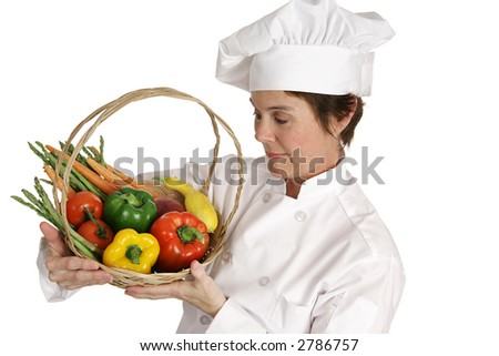 A chef inspecting a basket of fresh vegetables.  Isolated on white.