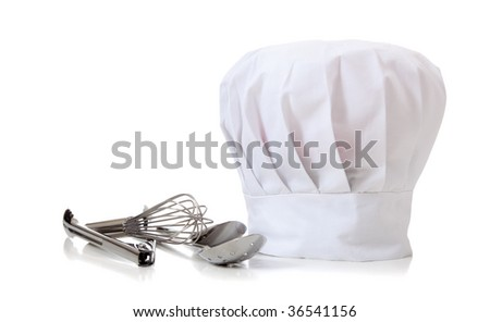 A chefs hat and utensils on a white background - stock photo