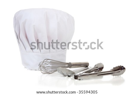 A chefs' kitchen tools including spoons, wisk, tongs and a toque or hat on a white background with copy space