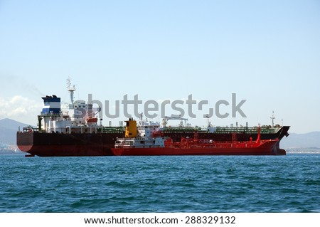 A chemical tanker which is anchored being refueled by a fuel barge at sea