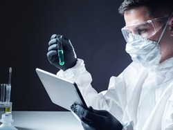 A chemist with an electronic tablet and a test tube. A man in a protective suit in the lab. Diagnosis of coronavirus. Medical test. Detection of diseases using tests.