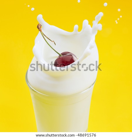 A cherry falling into milk creating a splash