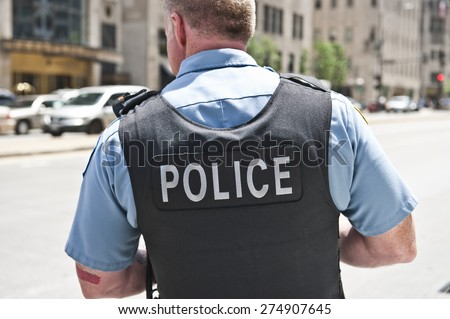 A Chicago city policeman standing on the road on a sunny day wearing a bullet proof vest mentioning Police on his body. On the background, cars and tall buildings are seen.