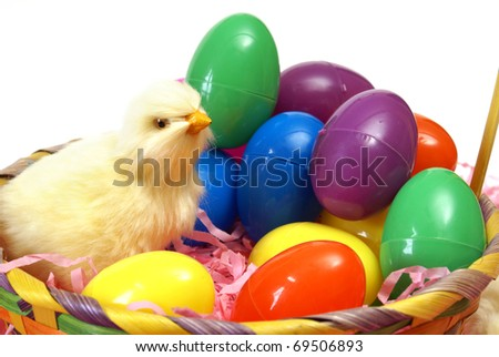 A chick with some easter eggs and a basket.