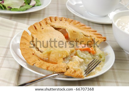 A chicken pot pie with a bowl of clam chowder and a green salad