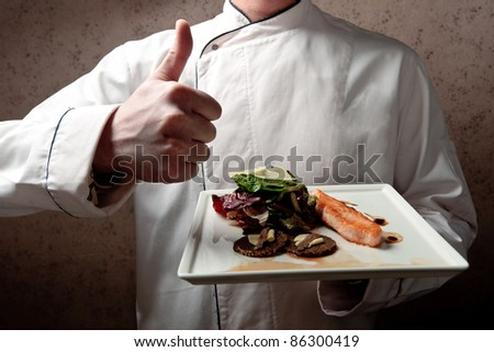 A chief dressed in white holding a white tray with roasted salmon fillet and vegetable salad elegantly decorated