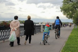 A child and father cyclists rides together on bicycles, grandmothers walking nearby along the embankment in Park on autumn day, back view on alleyway road, urban outdoors family vacation