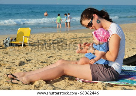 A child and her mother play in the sand together on the beach.  Concept photo of motherhood, newborn, baby, relationship, parenting, love ,care.