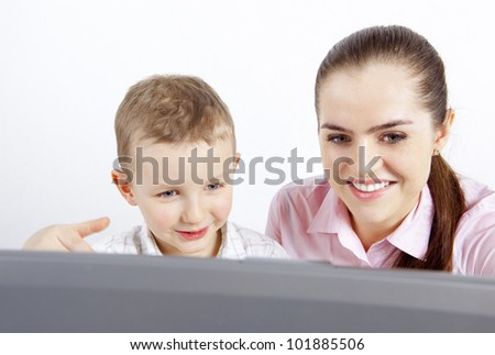 A child and laptop. The boy and a woman sit at the laptop. They are happy looking at the monitor.