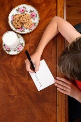 A child at desk writing a letter to Santa Claus, beside him a plate of choc chip cookies and glass of milk.
