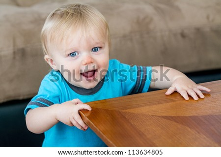 A child at the end of the table getting ready to turn the corner as he is learning how to walk.